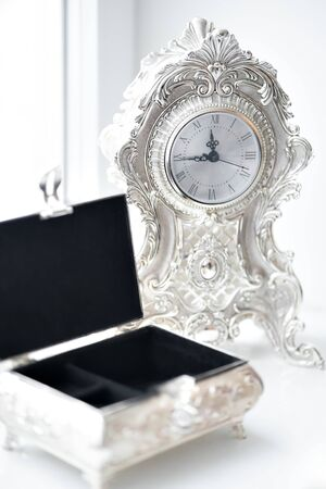 Photo pour An open vintage box for women's jewelry stands on a white window, near an old watch. - image libre de droit