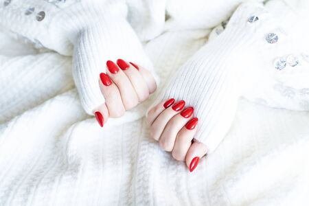 Photo pour Red fashion manicure on delicate female hands. Hands of a beautiful young woman on a soft white background. - image libre de droit