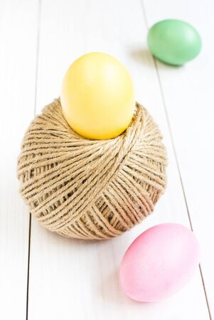 Easter egg and rolling ball of hemp rope on wooden background