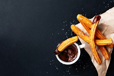 Foto für Churros with sugar dipped in chocolate sauce on a black background. Churro sticks. Fried dough pastry, top view - Lizenzfreies Bild