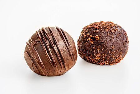 Photo pour Chocolate truffle candies covered with flowing chocolate and cocoa powder isolated on white background. Macro - image libre de droit