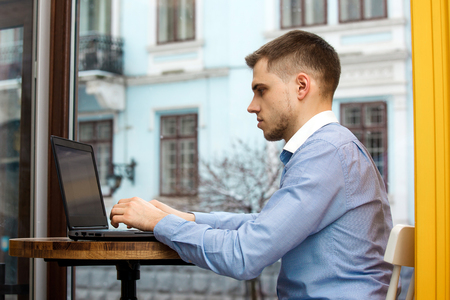 Photo pour Man use laptop connecting wifi internet, businessman busy at office desk, finger typing on computer sitting at wooden table in cafe with cup of coffee. - image libre de droit