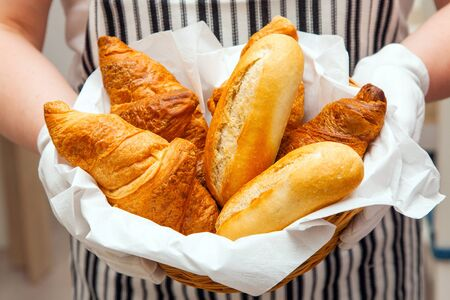 Foto de Fresh buns and croissants in basket on the canvas background. Baker dressed apron holds tasty and appetizing pastries for breakfast in hotel. - Imagen libre de derechos