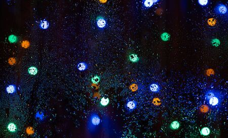 Photo for Rain drops on window with bokeh on blure background. Night on the street and a lot of multicolored lanterns behind wet glazing. - Royalty Free Image