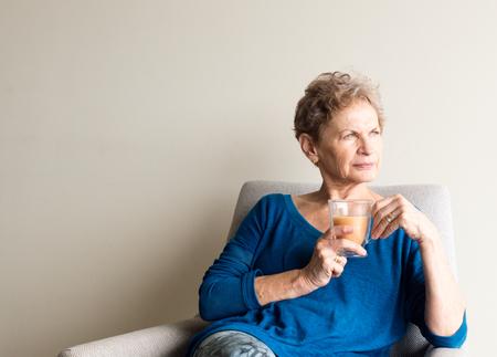 Foto für Older woman in blue top with cup of tea, sitting in chair and looking pensive - Lizenzfreies Bild