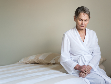 Foto für Elderly woman with short hair and white dressing gown seated on bed in bedroom looking pensive (selective focus) - Lizenzfreies Bild