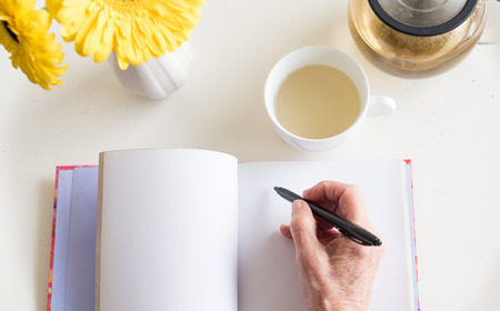 Photo pour High angle view of older woman's hand holding black pen on blank journal with cup of chamomile tea and yellow flowers (selective focus) - image libre de droit