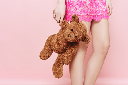 Fashion photo of young girl posing with Teddy bear over pink background in studio