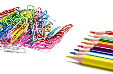 Photo pour Many multi-colored stationery clips for documents and multi-colored pencils lie on a white background. Close-up. top view - image libre de droit