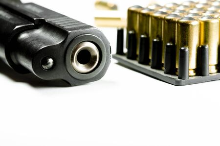 Foto de A black pistol with bullets for shooting lie on a white background. Guns and ammunition placed in a wooden table,Short guns and ammunition placed on a black background table,Guns and ammunition are ready to use.,Noisy weapon - Imagen libre de derechos