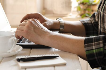 Foto de Freelancer works in the home office sitting at the desk near the window. Open laptop with blank screen on a white background top view - Imagen libre de derechos