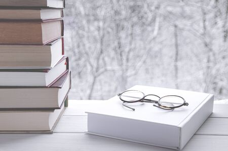 Old multi-colored books stand on a wooden shelf against the backdrop of the winter forest next to reading glasses