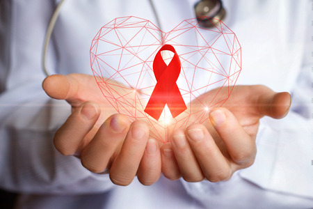 Ribbon for the fight against AIDS in the hands of the doctor.