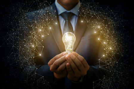 Foto de 2018 light bulb as an idea in the hands of the businessman. The concept of a new year. - Imagen libre de derechos