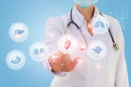 Photo pour Doctor chooses a heart among the organs on a blue background. - image libre de droit