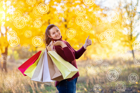 A happily smiling woman holding the multicolored shopping packages showing the positive gesture against the bright autumn background with flying percents around. The concept is the profitable sale shopping.