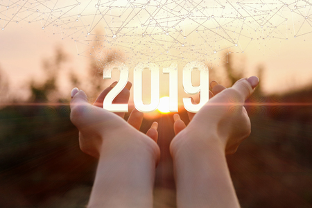 Foto de The numbers of coming year are in the open palms at the sunset background. The concept is the symbol numbers of future year. - Imagen libre de derechos