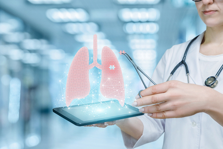 Foto de A doctor is putting missing puzzle piece by means of medical clamp into digital lungs model hanging above a tablet in her hand. The innovative approach in dangerous diseases treatment. - Imagen libre de derechos