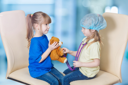A closeup of children playing patient and pediatrician who is touching a toy bear with her stethoscope while sitting opposite each other at the blurred background. The pediatrician medicine concept.