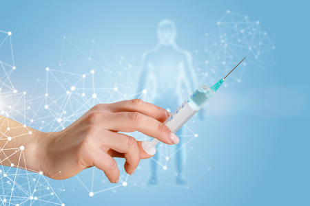 Photo pour A female hand holding a vaccination syringe with substance within wireless connections and with the human figure model behind at light background. The compulsory vaccination and treatment concept. - image libre de droit
