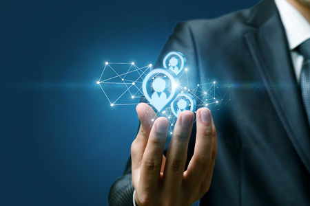 Photo pour A closeup of hand of a businessman holding a structure of wireless connections and human figures images models at dark background. The concept of potential clients. - image libre de droit