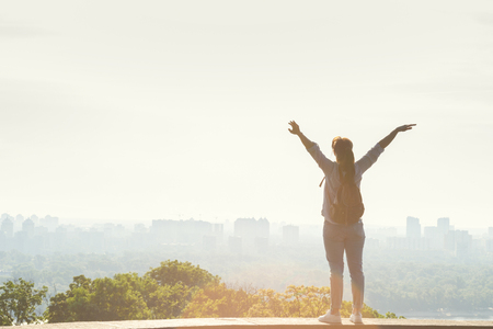 Photo pour Woman with arms outstretched on the background of the city panorama. - image libre de droit