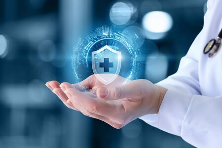 Photo for The doctor shows the icon of the protection of health on blurred background. - Royalty Free Image
