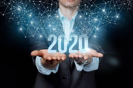 Photo pour The new concept 2020 in the business. Businesswoman showing 2020 on a black background. - image libre de droit
