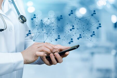 Photo pour The doctor working at the medical network on the mobile device. - image libre de droit