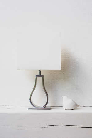 Photo pour A white lamp and a sculpture of a white bird are on a shelf in the house against the background of a white wall. - image libre de droit