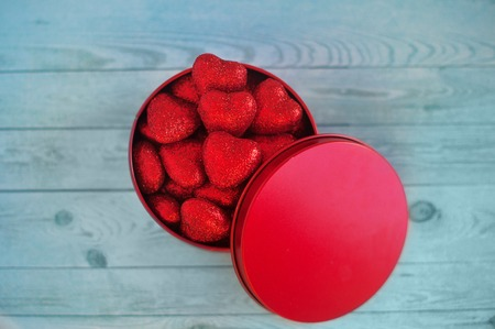shiny red hearts in a gift box on a wooden background
