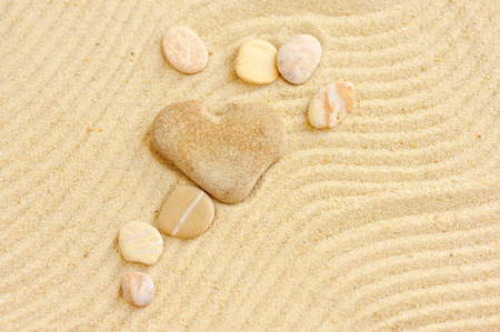 Heart shaped stone is on sand