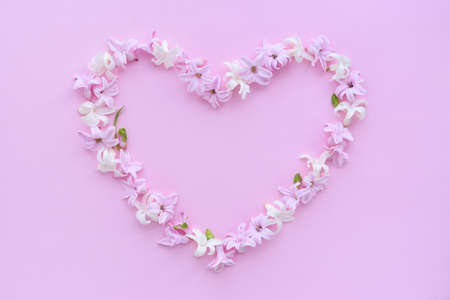 Photo pour Heart symbol made of fresh hyacinth flowers on pink background. Flat lay, top view, copy space - image libre de droit
