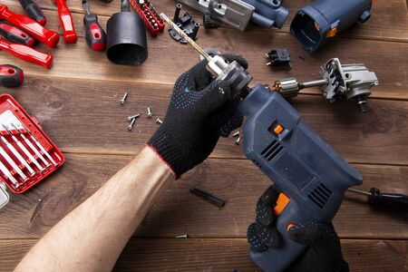Photo pour the master repairs a broken electrical device: drill, cutter on a wooden table. Electric Tool Repair Shop. - image libre de droit