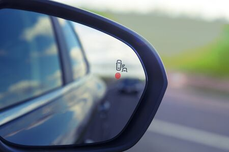 Photo pour Blind Spot Monitoring system warning light icon in side view mirror of a modern vehicle. - image libre de droit