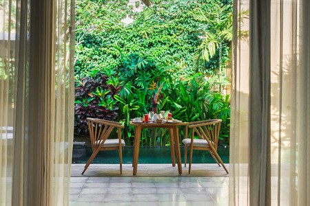 Foto de Beautiful cozy luxury breakfast for two at the private pool, Bali,Indonesia.A wooden table with an abundant healthy breakfast on the background of the pool and tropical plants. - Imagen libre de derechos