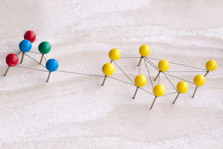 Communication concept inside a group of people. Family, work, business, network connections. Needles with colored heads and threads between them
