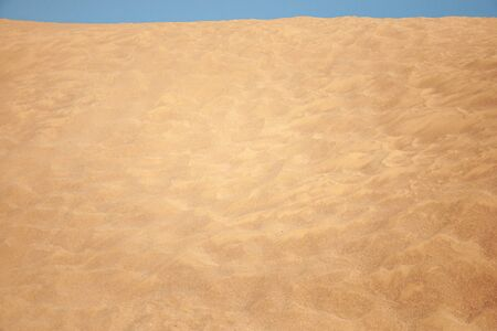 Yellow sand and blue cloudless sky in the desert. Travels