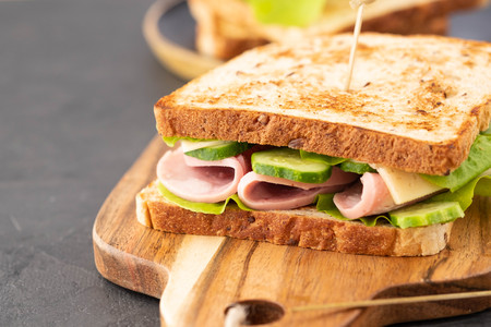 Photo pour Close-up photo of a club sandwich. Sandwich with meet, prosciutto, salami, salad, vegetables, lettuce on a fresh sliced bread on wooden background. - image libre de droit