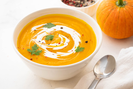 Foto de Pumpkin soup with cream and pumpkin seeds isolated on white background. Autumn concept. - Imagen libre de derechos