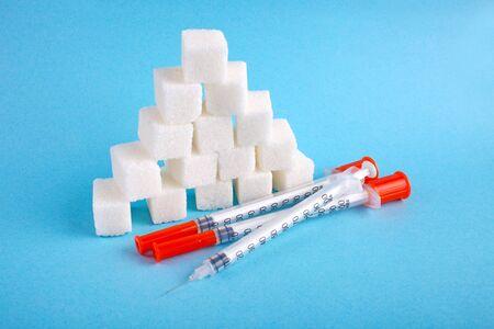 Foto de Three insulin syringes and lump sugar on a blue background. World Diabetes Day, November 14. Diabetes concept. - Imagen libre de derechos