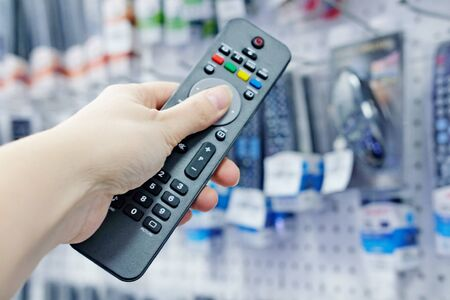 a person's hand presses the control buttons of the TV's black remote control at their leisure with a finger to change the LCD video channel. Selecting and purchasing a remote control in the sto