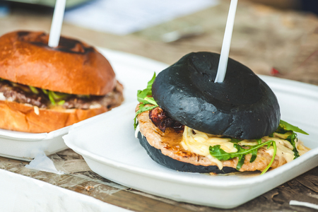 Hamburger grilled with a black bun in the open air