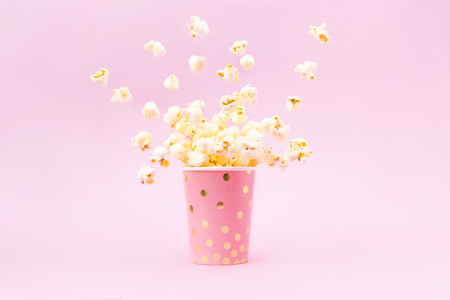 Foto de Flying Popcorn in a bright glass and on a pink background. Copy space - Imagen libre de derechos