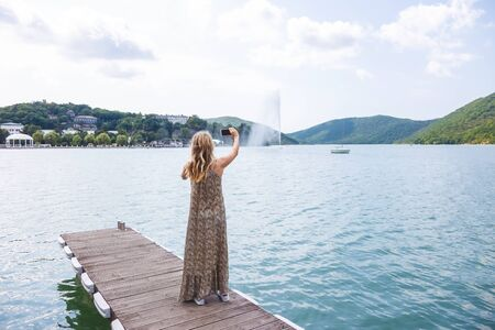 Photo for girl blogger traveler takes pictures on smartphone beautiful mountain lake and yachts - Royalty Free Image
