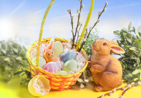 Photo for Easter decoration. Easter basket with flowers, eggs and cute Easter bunny on a pastel pink background. - Royalty Free Image