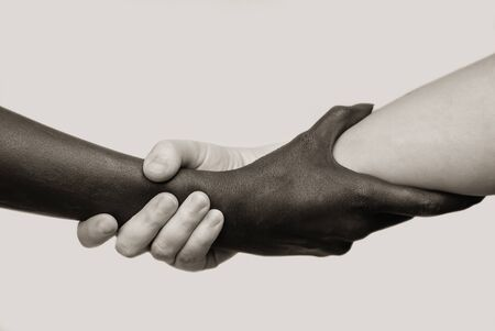 Photo for Black-and-white human arms wrapped tightly around each other . The concept of combating racism, friendship and respect .Selective focus, close-up, black and white photography, isolated background - Royalty Free Image