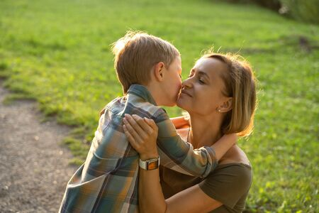 Photo for Beautiful young mother with little son walking in the park after a rain - Royalty Free Image