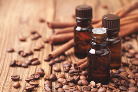 Glass bottles with essential oils of coffee and cinnamon on wooden background