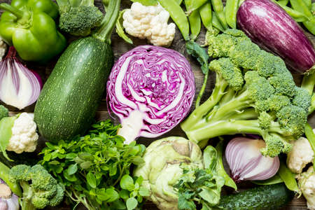 Photo pour Top view set raw of green, red and purple vegetables spread on dark wooden background - image libre de droit